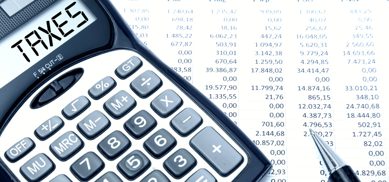 Calculator with TAXES text  with calculation sheet background